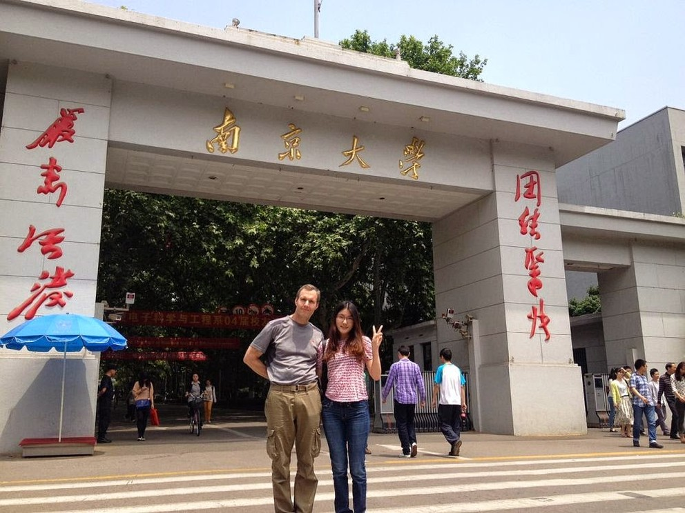 Two members of the Asian Studies Department stand in front of the building they are working at